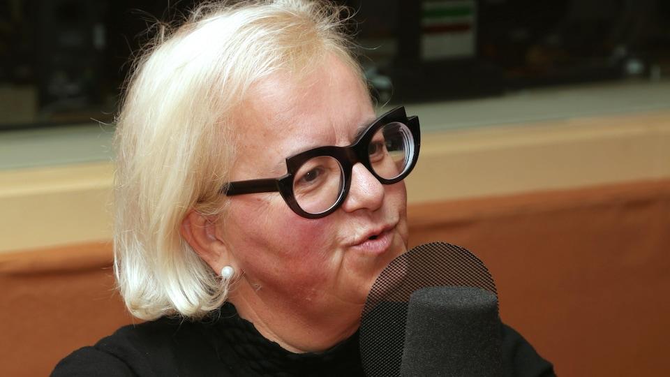 Photo de Francine Laplante qui parle dans un micro de radio.