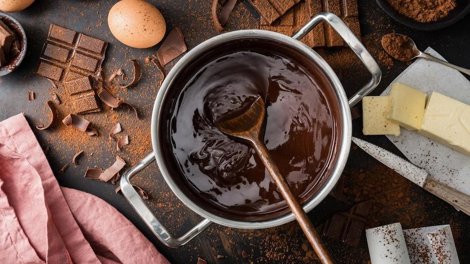 Du beurre, des œufs, du cacao en poudre, des tablettes de chocolat et une casserole de chocolat fondu sur une table.