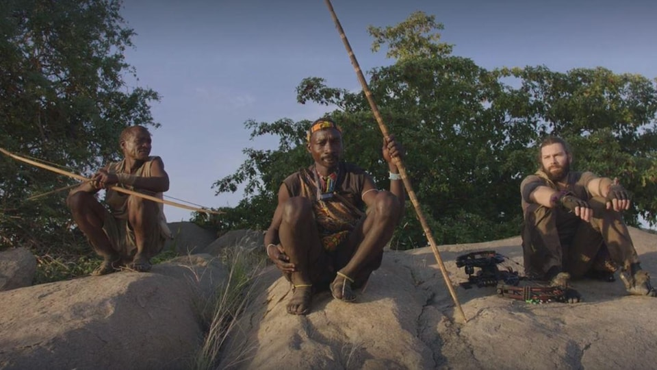 Trois hommes assis sur un rocher.