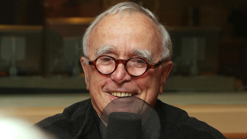 Jean-Claude Guillebaud devant un micro de radio.