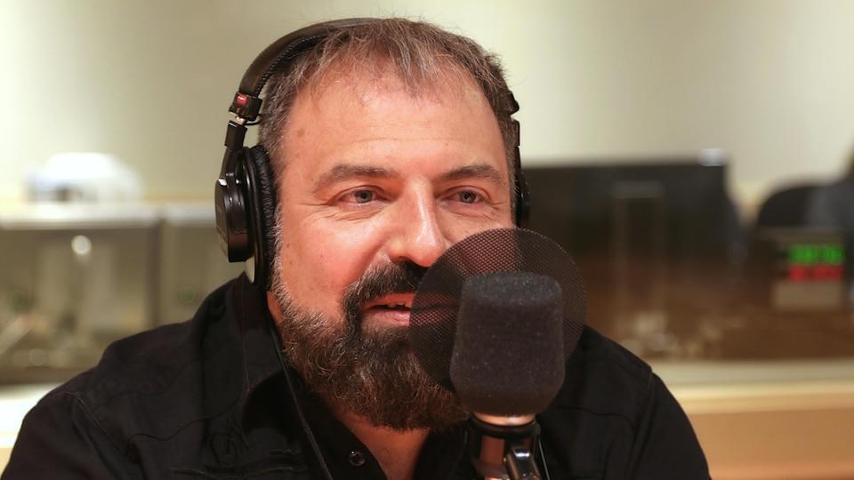 Jean-François Mercier devant un micro de radio.
