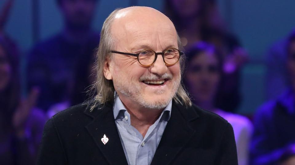 Il sourit sur le plateau de l'émission de télévision Tout le monde en parle.
