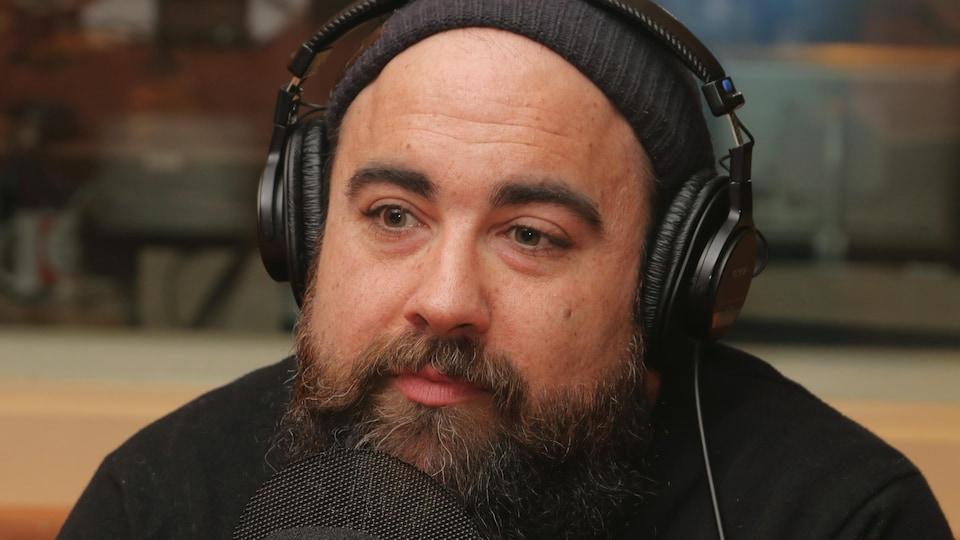 Photo de Jonathan Roberge devant un micro de radio.