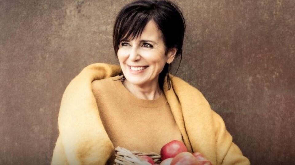 Photo de Josée di Stasio qui pose avec un panier de pommes.