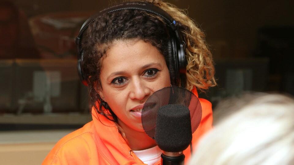 Photo de Nadia Essadiqi devant un micro de radio.
