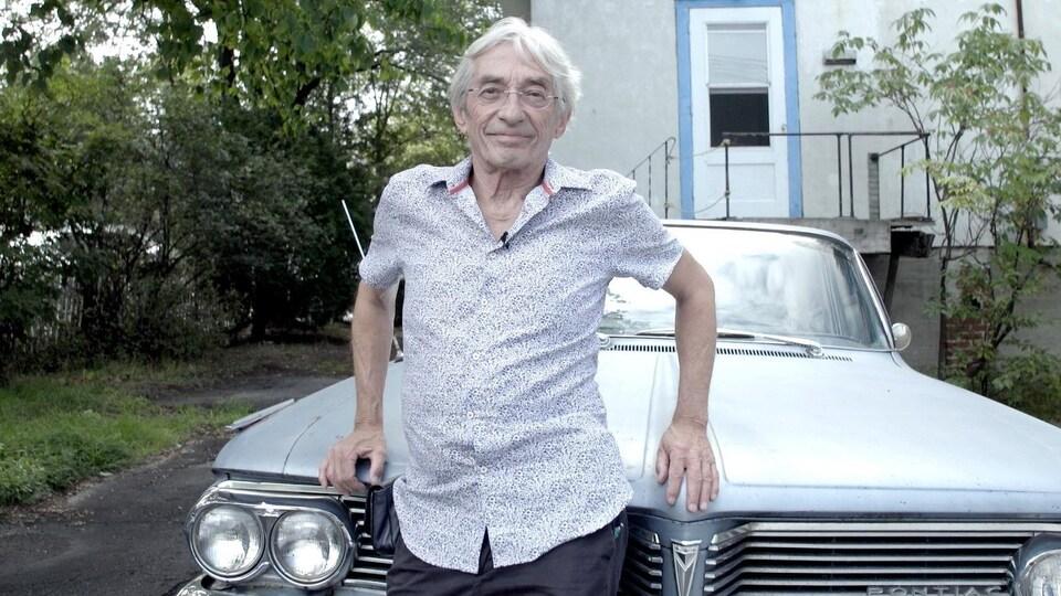 Il pose devant le capot d'une voiture Pontiac.