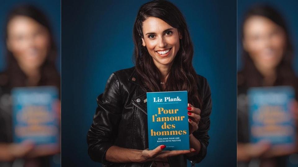 Elle pose en tenant dans ses mains son livre « Pour l'amour des hommes ».