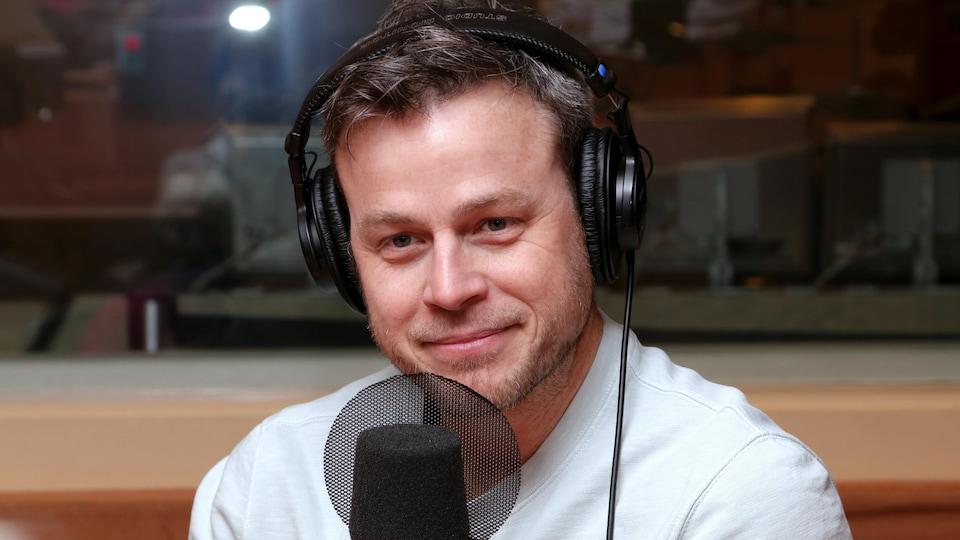 Louis Morissette souriant devant un micro de radio.