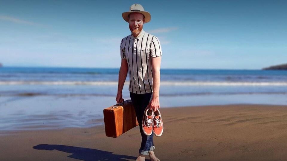 Il est pieds nus sur une plage et tient ses chaussures dans une main et une valise dans l'autre.
