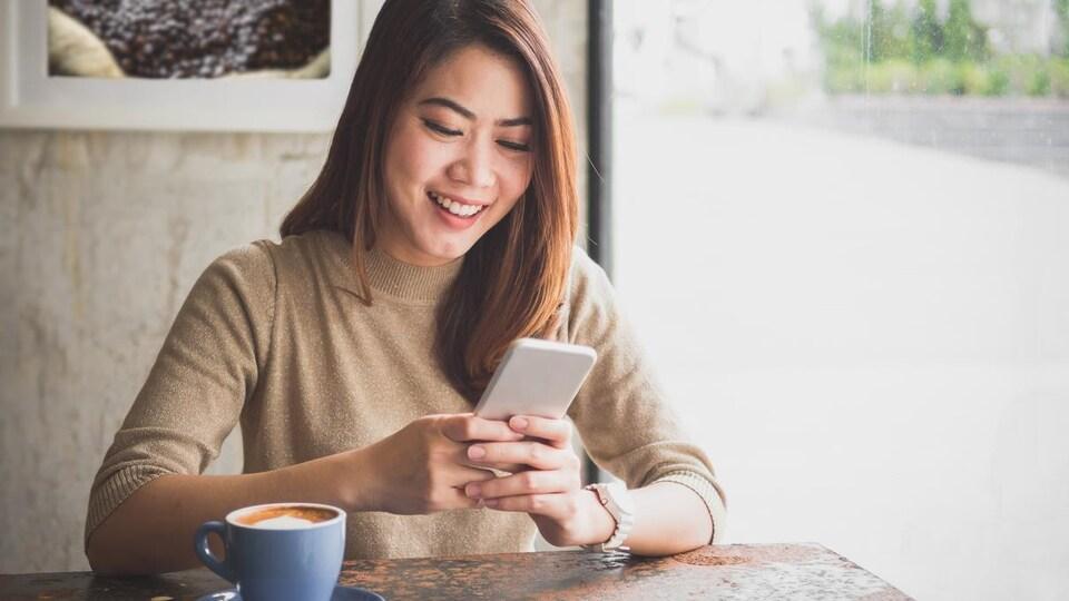 Une jeune femme consulte son téléphone, assise à la table d'un café.