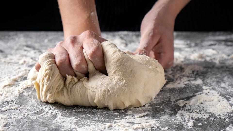 Deux mains pétrissent une pâte à pain.
