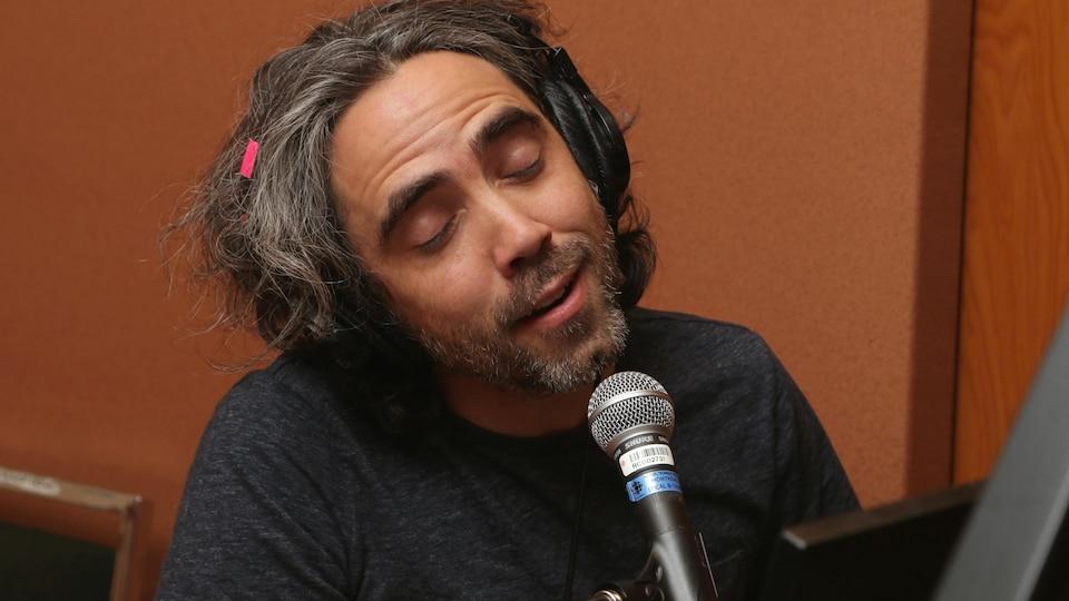 Photo de Patrick Watson, les yeux fermés, qui joue au piano et chante dans un micro.