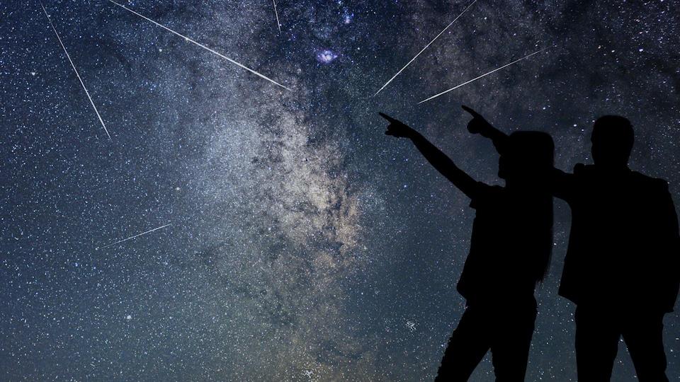 Silhouette de deux humains qui regardent une pluie d'étoiles filantes.