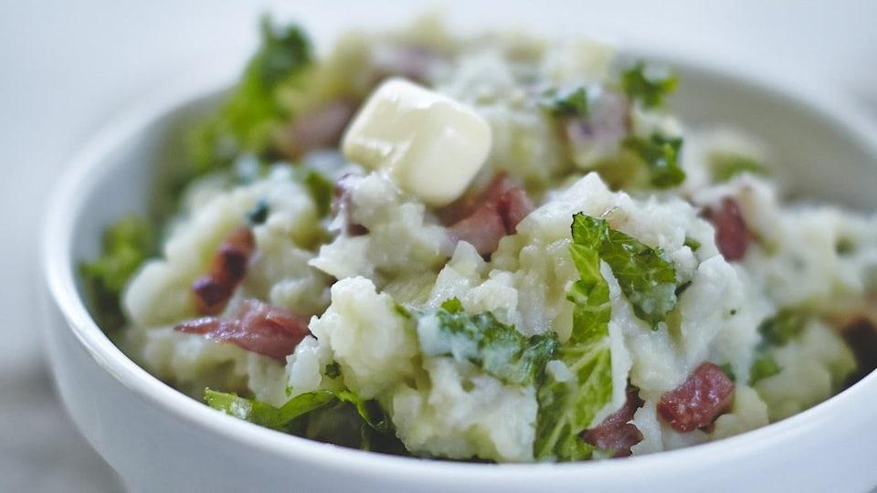 Purée de pommes de terre, chou et jambon servie dans un bol avec un morceau de beurre.