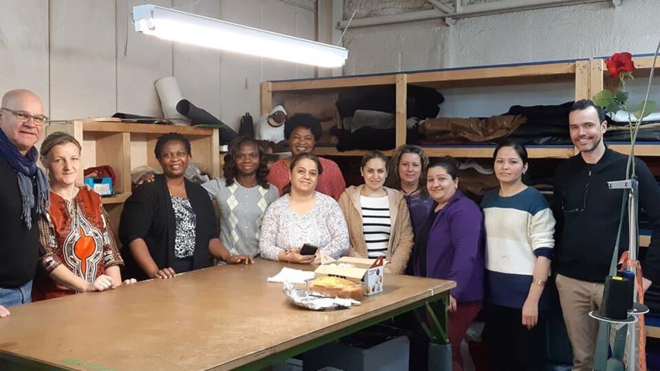 Photo où une dizaine de femmes et d'hommes posent dans un atelier autour d'une grande table.