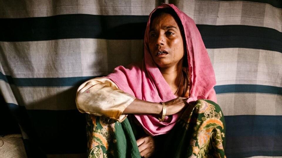 Photo d'une femme assise par terre, une larme coule sur sa joue.