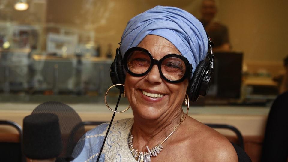 Portant un boubou et un turban bleu, Francine Grimaldi sourit en studio.