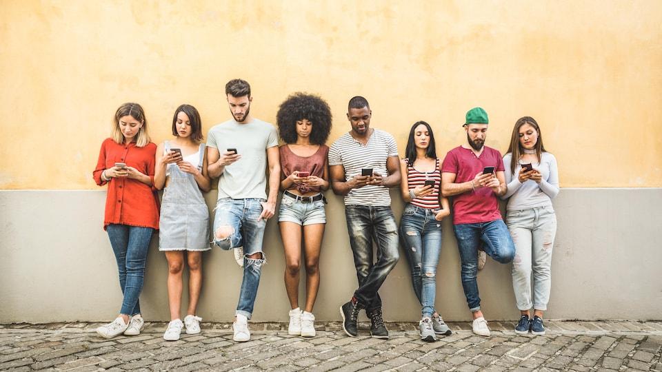 Un groupe de jeunes personnes accotées sur un mur, toutes sur leur téléphone cellulaire.