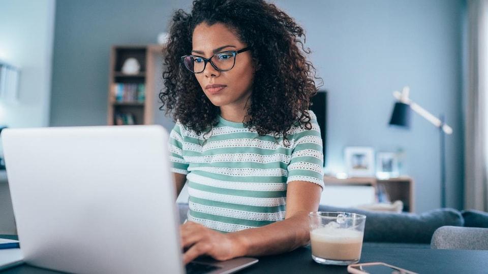 Une femme travaille sur un ordinateur portable dans son salon.