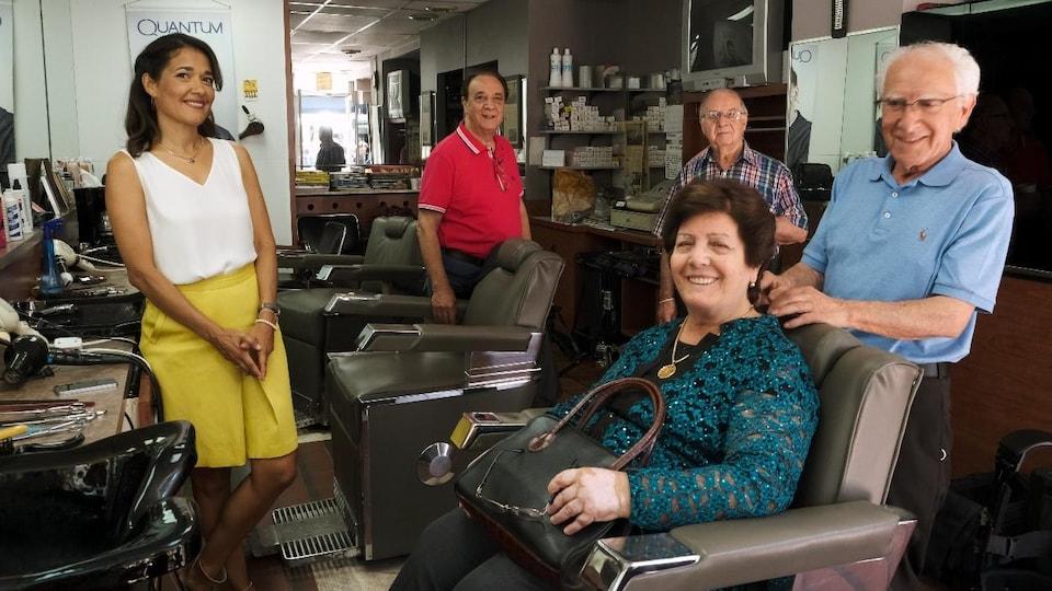 Sophie Fouron pose avec les trois barbiers dans leur salon de coiffure et une femme qui se fait coiffer.