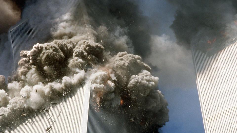 On voit en contre-plongée le gratte-ciel qui se rompt près de son sommet, la partie supérieure s'effondrant en position oblique, créant un immense nuage de fumée et de poussière.