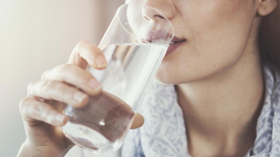 Une femme boit un grand verre d'eau.