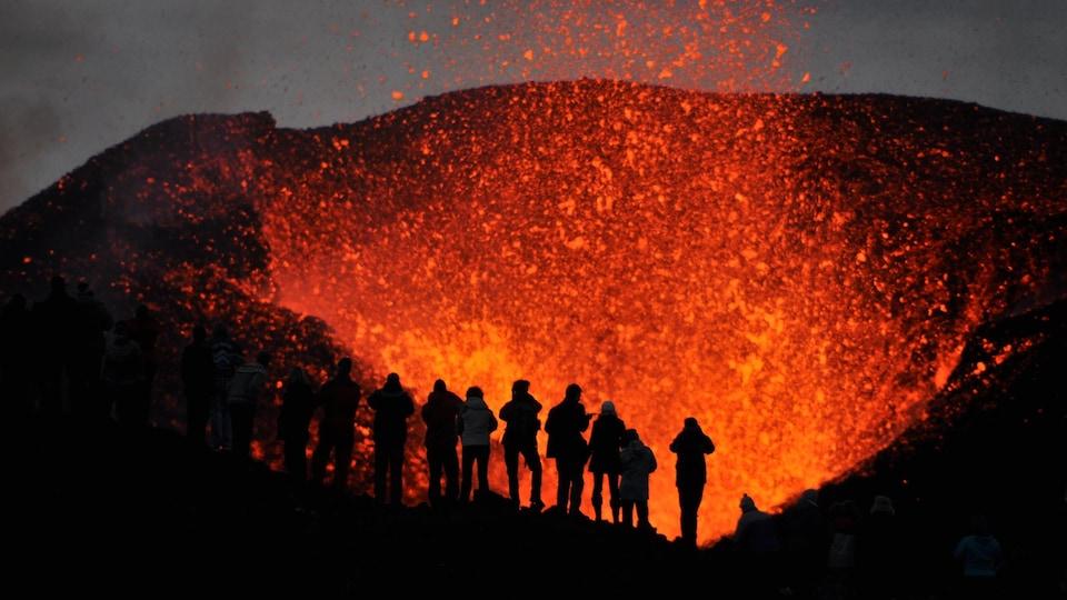 Des silhouettes se dessinent sur fond de volcan en éruption.