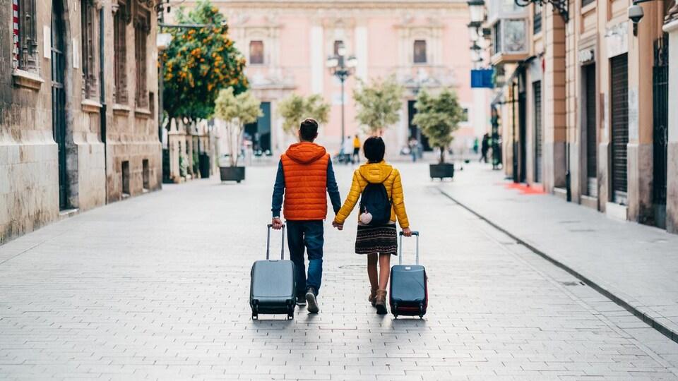 Un jeune couple marche en se tenant la main et en tirant ses valises dans les rues de Valence, en Espagne.