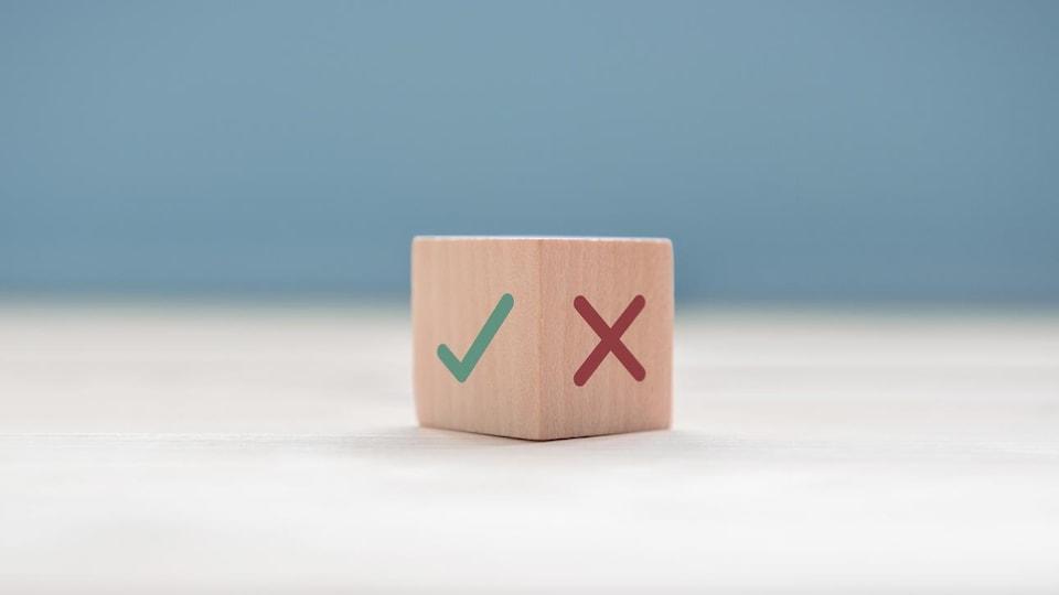 Un cube de bois avec une coche verte et une croix rouge sur deux de ses côtés.