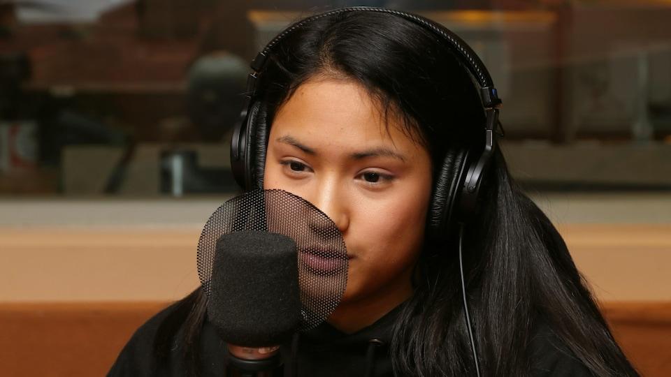 Elle est devant un micro de radio.
