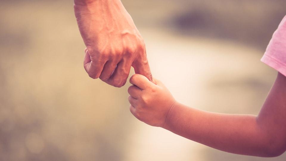 Une père et sa fille se prenant la main