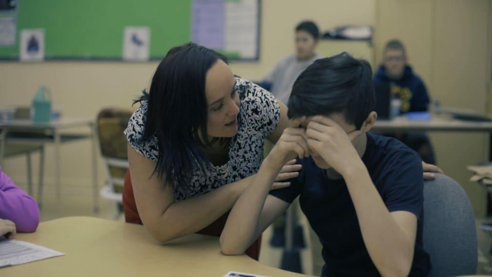 Une enseignante tente de réconforter un élève.