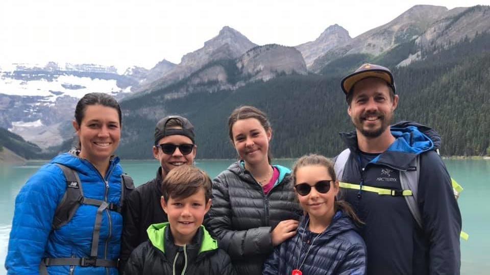 Portrait de deux adultes et quatre enfants souriant et posant près d'un lac au pied de hautes montagnes.