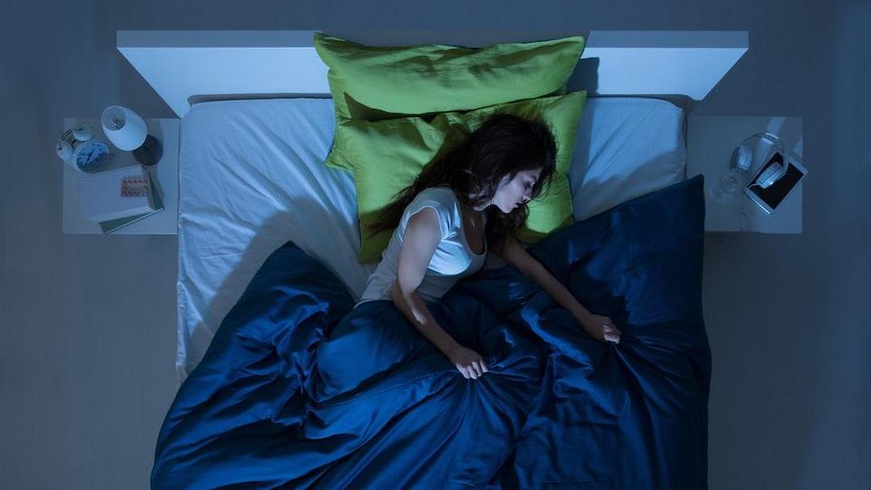 Une femme endormie seule dans un lit.