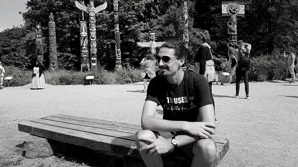 Benjamin Doudard assis sur un banc au parc Stanley, à Vancouver.