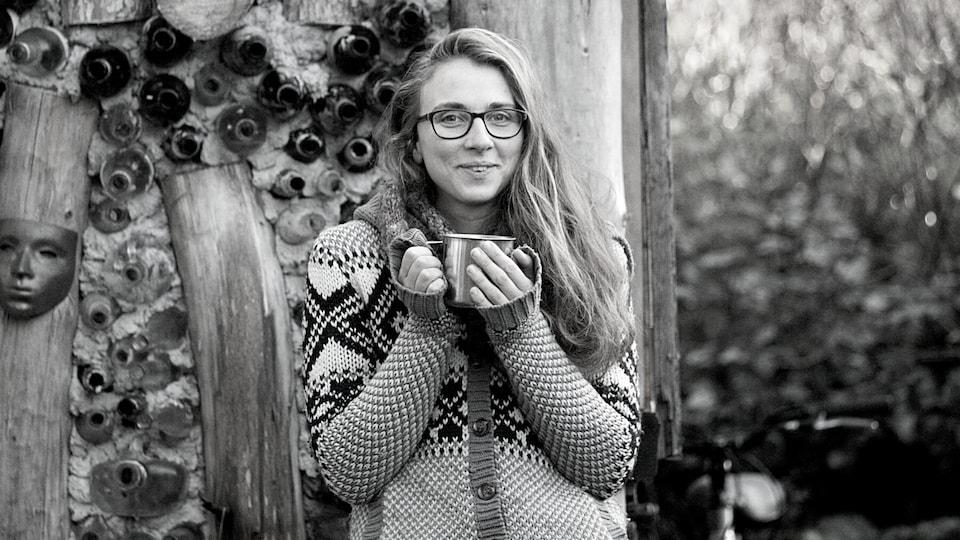 Donna Talluto près d'une cabane dans la forêt tient une tasse dans ses mains.