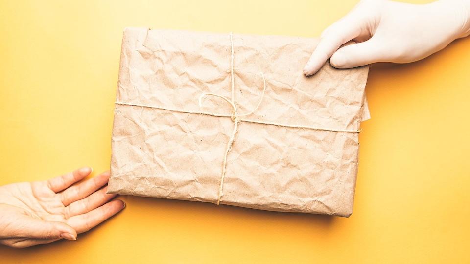 Une main gantée tient un colis recouvert de papier brun.