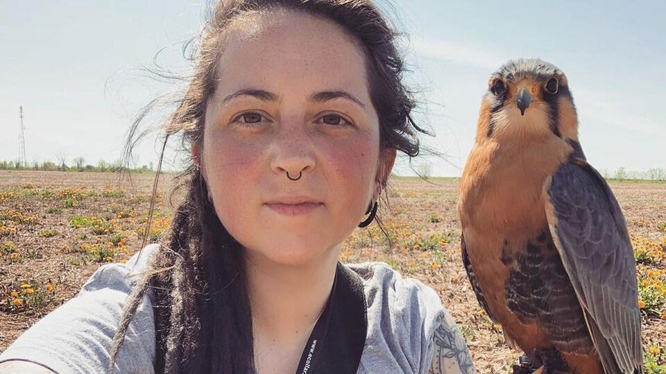 Selfie d'une femme avec son faucon perché sur sa main.