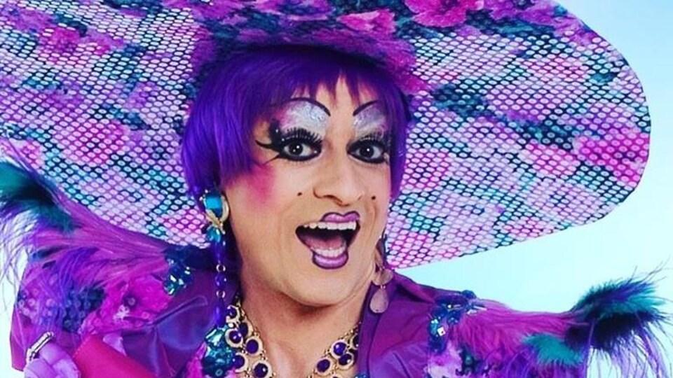 La drag queen Mado Lamotte est habillée en mauve avec un très grand chapeau fleuri.