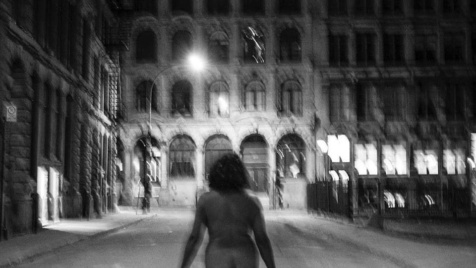 Photo en noir et blanc d'une femme nue dans les rues de Montréal.