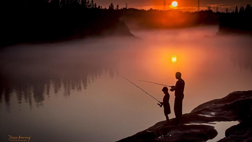 Un père et son fils sur le bord d'un lac, en train de pêcher, au coucher de soleil.
