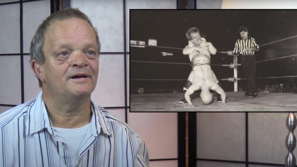 Pierre Therrien en entrevue à la caméra. Une image d'archives de Pierre Therrien prenant part à un match de lutte est superposée à l'entrevue.