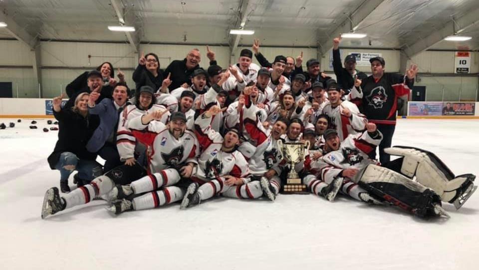 Une équipe de hockey pose sur la glace avec le trophée des champions.