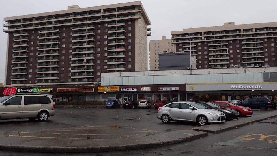 Des tours d'habitation devant lesquelles se trouvent un centre d'achats et un grand stationnement.