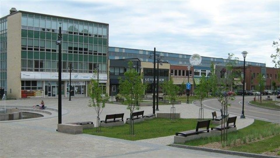 La Place La Salle à Baie-Comeau : un lieu avec une fontaine, des bancs, des arbres et des commerces.