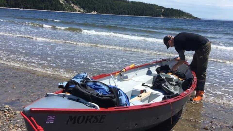 Un homme prépare son bateau sur le bord de la mer.
