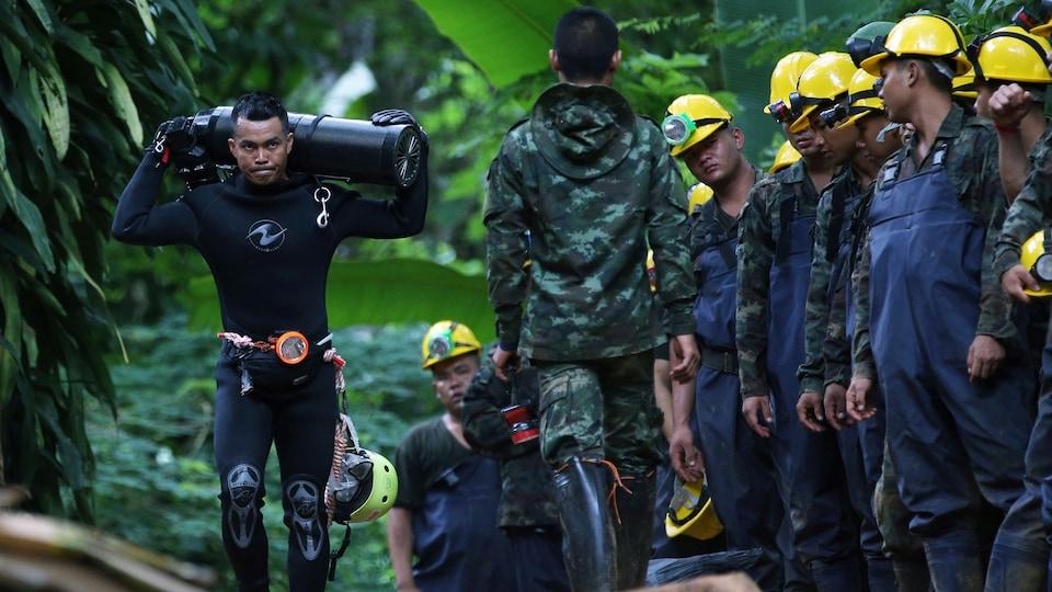 Un plongeur porte une bonbonne d'oxygène en passant devant plusieurs ouvriers.
