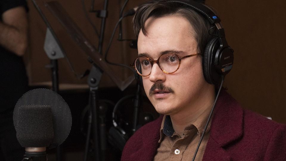 Le poète se présente, lunettes rondes sur le nez.