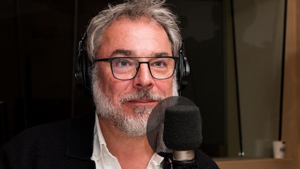 Affublé de lunettes, le comédien écoute attentivement l'animatrice.