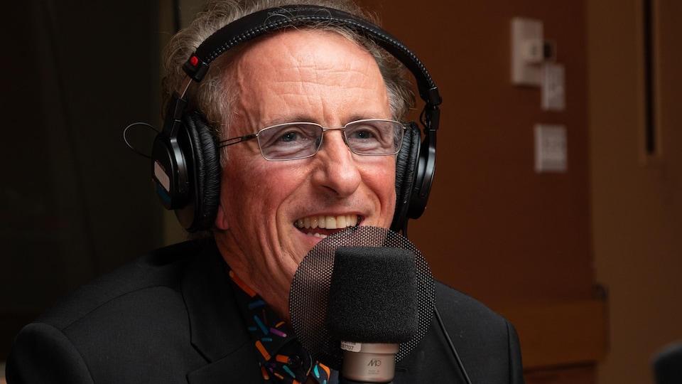 Le musicien aux lunettes bleutées sourit à l'animatrice.